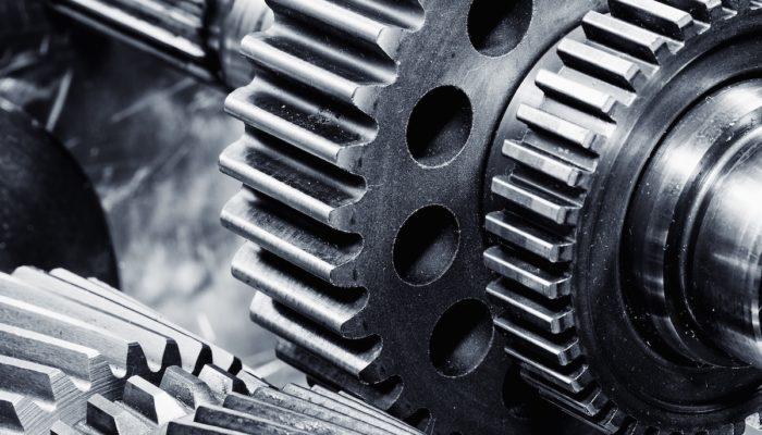gears and cogwheels set against brushed aluminum, aerospace engineering